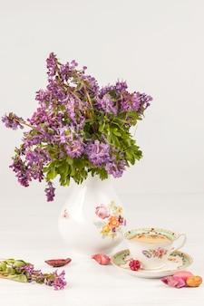 Thee met citroen en boeket van lila primula's op tafel