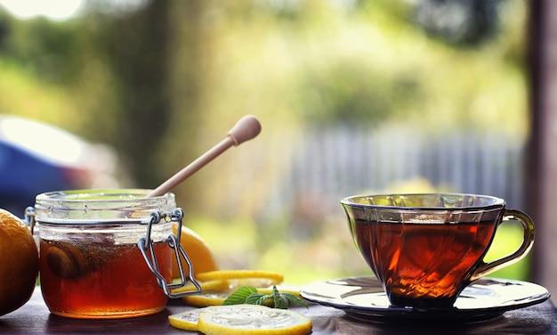 Thee met citroen en munt in de natuur. een kopje hete muntthee met citroen en honing in pot. citroenschijfjes en een lepel met honing tot hete thee.