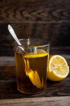 Thee met citroen in een glas op een houten achtergrond.