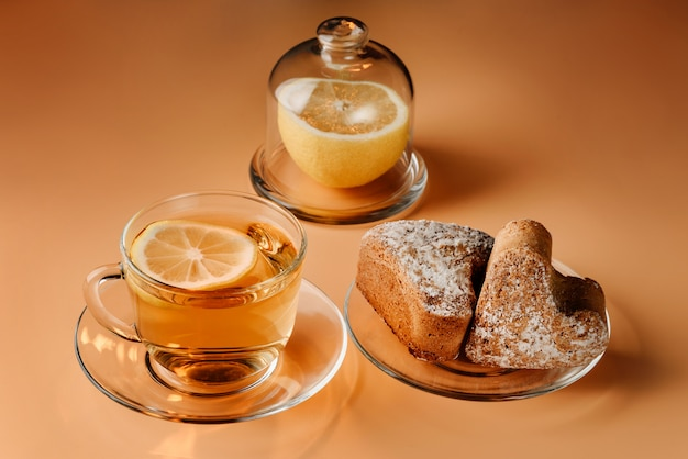 Thee met citroen, kwark muffins en citroen op een lichte achtergrond.