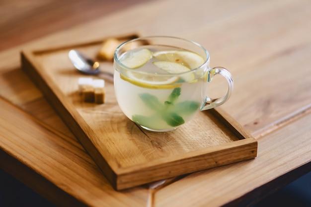 Thee met citroen op een houten tribune met koekjes