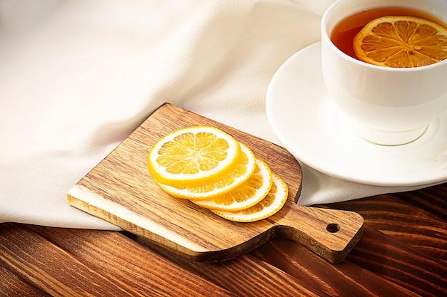 Thee met citroen op een lichte en houten tafel