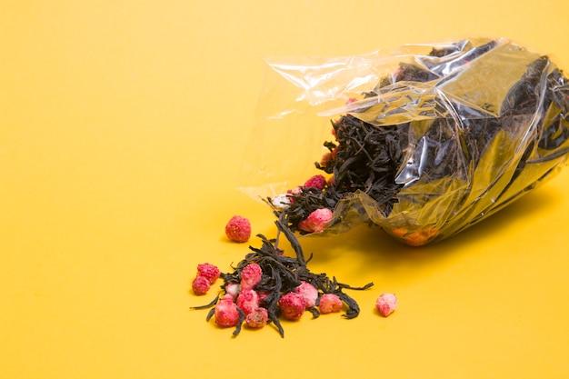 Thee met droge aardbeien in een plastic zak op een gele achtergrond, kopieer plaats