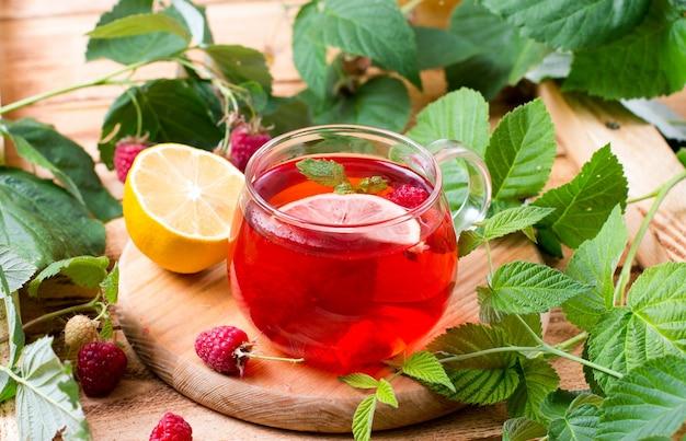 Thee met frambozen in een glazen beker op het houten bord