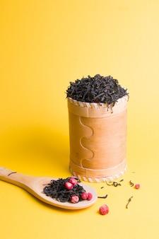 Thee met gedroogde aardbeien in een houten pot op een gele achtergrond