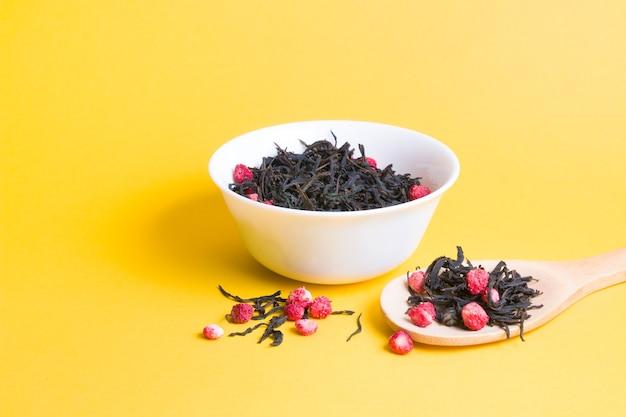 Thee met gedroogde aardbeien in een witte kom, aardbeienthee in een grote houten lepel op een gele achtergrond, kopieer ruimte