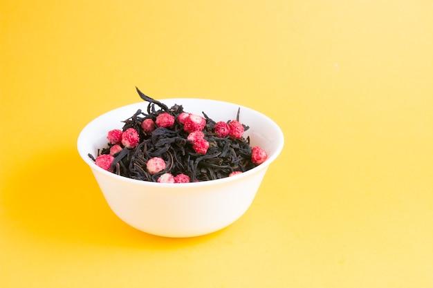 Thee met gedroogde aardbeien in een witte kom op een gele achtergrond