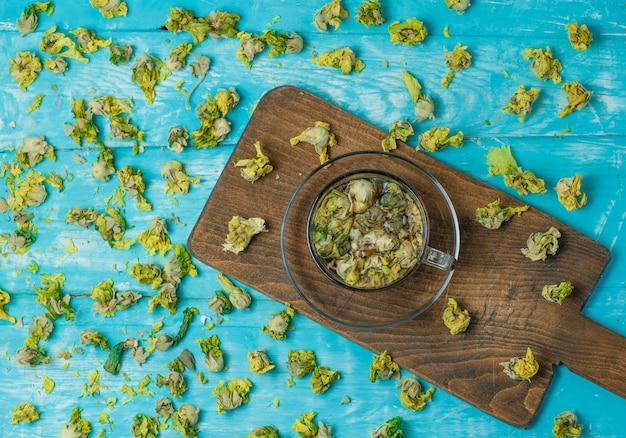 Thee met gedroogde kruiden in een glazen mok op blauw en snijplank, bovenaanzicht.