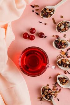 Thee met gedroogde kruiden, kersen in een glazen mok op roze en textiel.