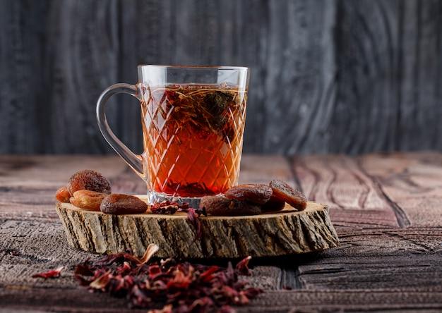 Thee met gedroogde vruchten en bloemen, citroen op hout in een kopje op stenen tegels en houten oppervlak