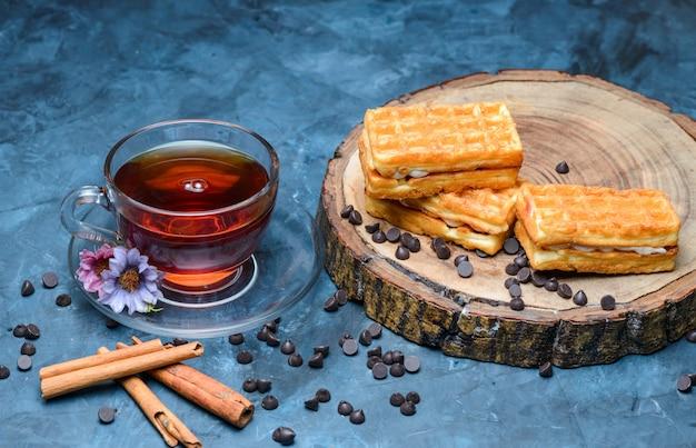 Thee met kaneelstokjes, wafel, choco chips, bloemen, houten plank in een kopje op blauwe ondergrond, hoge hoek bekeken.