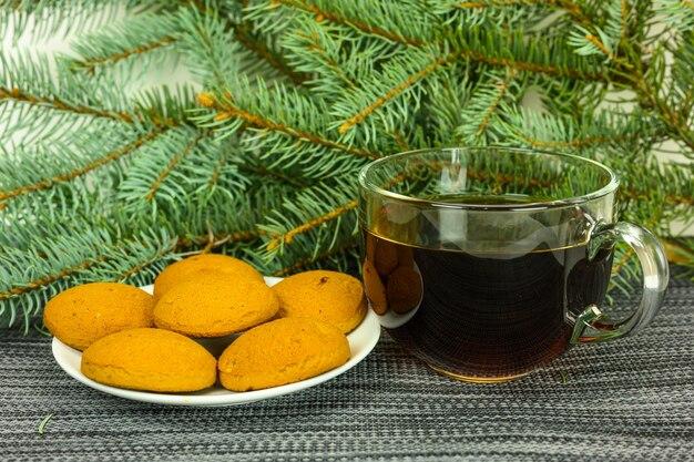 Thee met koekjes op de achtergrond van dennentakken.