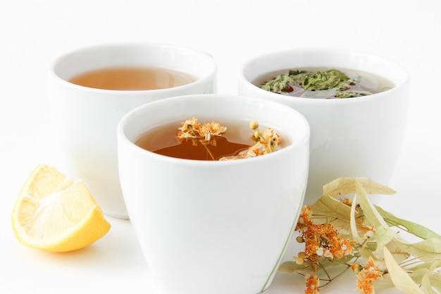 Thee met kruiden citroen en gedroogde linde bloemen op een wit bord in witte kopjes