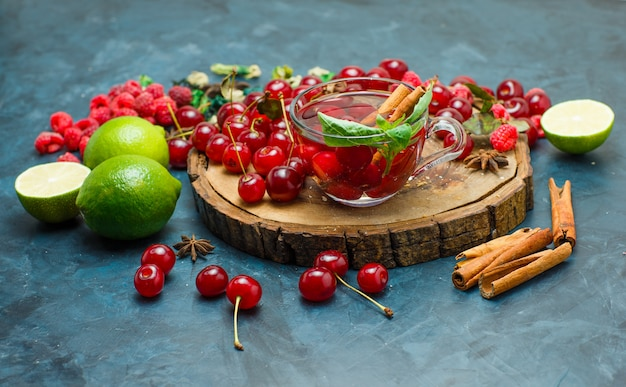 Thee met kruiden, fruit, specerijen in een mok op een houten bord en stucwerk achtergrond, hoge hoekmening.