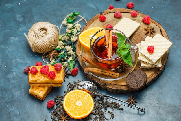 Thee met kruiden, fruit, specerijen, koekjes, zeef, draad in een mok op een houten bord en stucwerk achtergrond, plat leggen.
