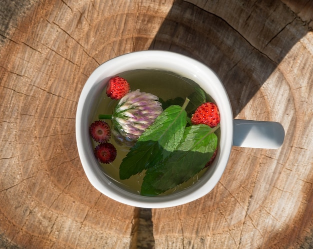 Thee met munt en aardbeien in een wit kopje