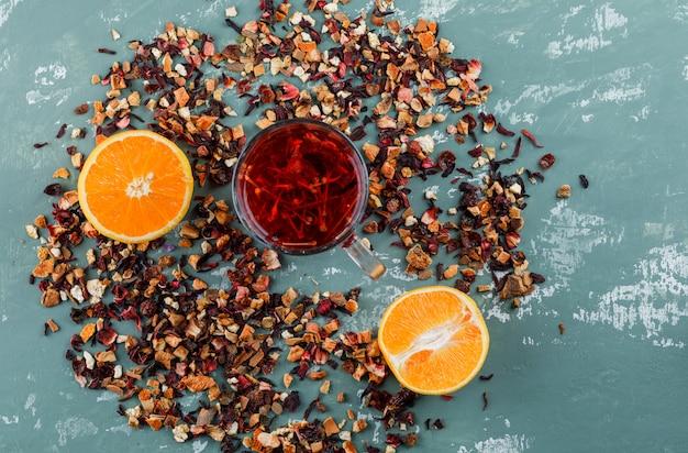 Thee met oranje, gemengde gedroogde kruiden in een kopje op gips oppervlak, bovenaanzicht
