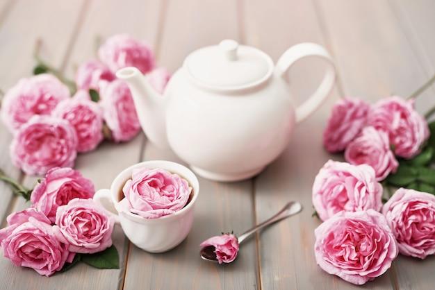 Thee met roze rozen op grijze houten tafel, kopie ruimte.