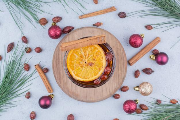 Thee met rozenbottels en kerstballen op marmeren oppervlak.