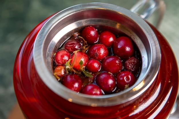 Thee met veenbessen en kruiden in een glazen theepot. een gezond dieet rijk aan vitamines en antioxidanten. levensstijl.