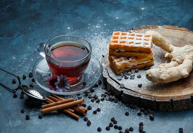 Thee met wafel, choco chips, kruiden, zeef in een kopje op blauwe grunge en houten plank oppervlak, hoge hoek bekeken.