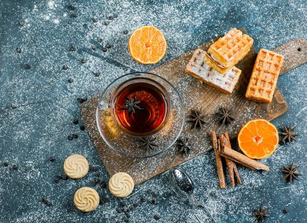 Thee met wafel, koekje, specerijen, choco chips, zeef, sinaasappel in een kopje op blauw en snijplank oppervlak, plat lag.