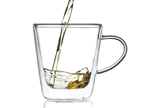 Thee of sap wordt gegoten in een transparante glazen beker op een witte achtergrond. close-up van een korte belichting.