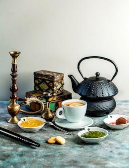 Thee-opstelling met zwarte thee, theepot, waterpijp, jam