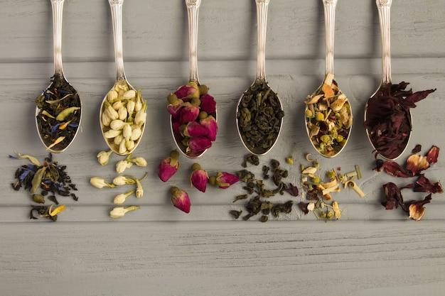 Thee samenstelling. verschillende soorten thee in de zilveren lepels op de grijze houten achtergrond. bovenaanzicht. kopieer ruimte.