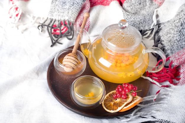 Thee van bessen van een duindoorn en viburnum met toevoeging van honing op het bed