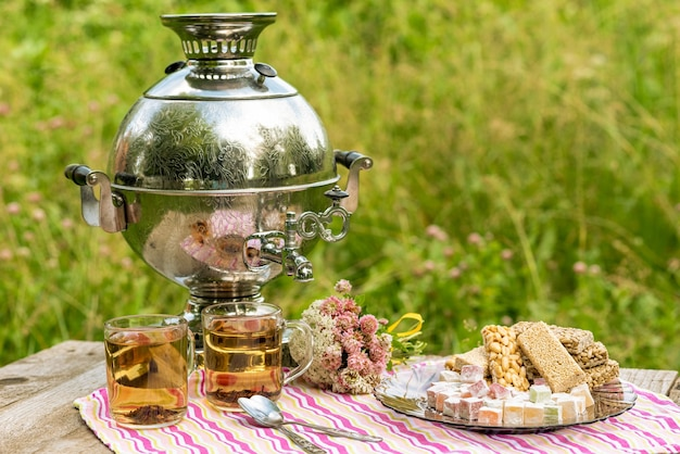 Thee van een samovar met verschillende zoetigheden in de natuur.