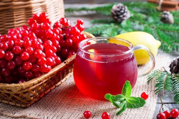 Thee van verse rode viburnum in een transparant glas, in de buurt van tak met bessen van viburnum