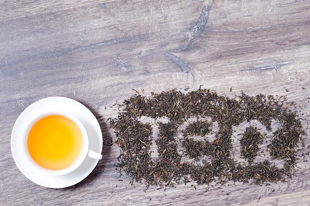 Thee woord gemaakt van groene thee bladeren op houten achtergrond