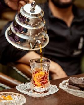Thee wordt van stalen theepot in kristalarmudu-glas gegoten