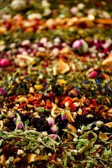 Theeachtergrond: groen, zwart, bloemen, kruiden, munt, melissa, gember, appel, roos, lindeboom, fruit, sinaasappel, hibiscus, framboos, korenbloem, cranberry. assortiment van droge thee, bovenaanzicht.