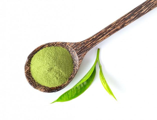 Theeblad en poeder van de matcha het groene thee in houten lepel die op witte achtergrond wordt geïsoleerd. bovenaanzicht