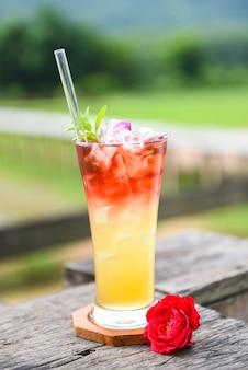 Theebloemen gemaakt van thee rozenblaadjes in een glas ijsthee met een theeroos koude cocktail