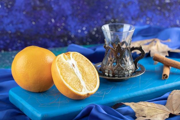 Theeglas en biologische citroen, heel of half gesneden.