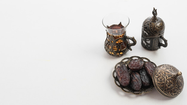 Theeglas en droge sappige dadelpalmvruchten of kurma op ramadan voedsel over witte achtergrond