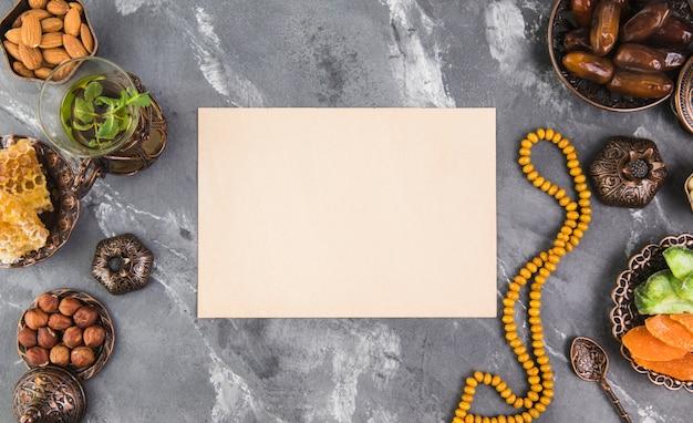 Theeglas met dadelsfruit, kralen en blanco papier