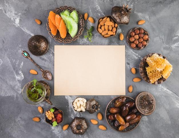 Theeglas met dadelsfruit, noten en blanco papier