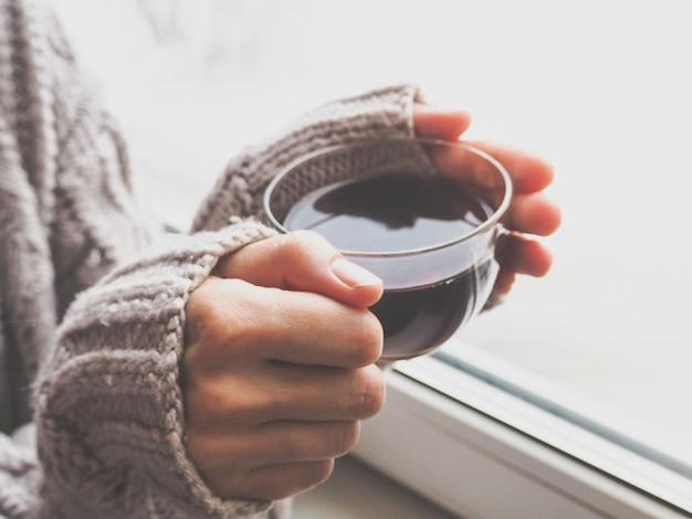 Theekop in vrouwelijke handen. het comfort van thuis met een kopje thee bij het raam.