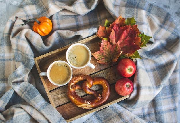 Theekop met koffie warme chocolademelk herfsttijd bakkerij pretzel gestemde sjaal deken gele bladeren grijs