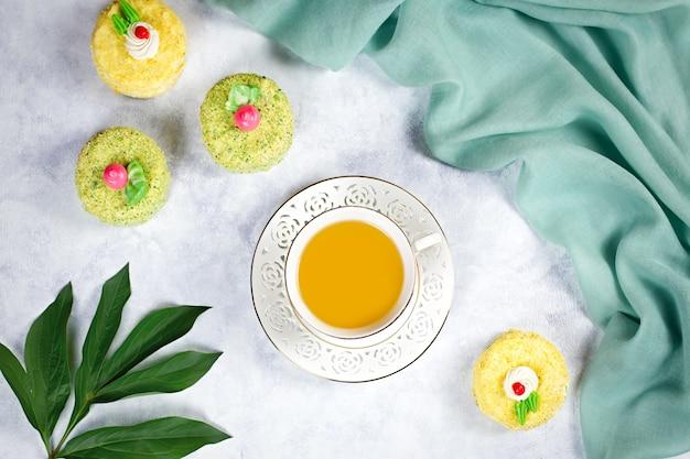 Theekop met kruidenthee en kleurrijke cakes. theekransje concept, bovenaanzicht