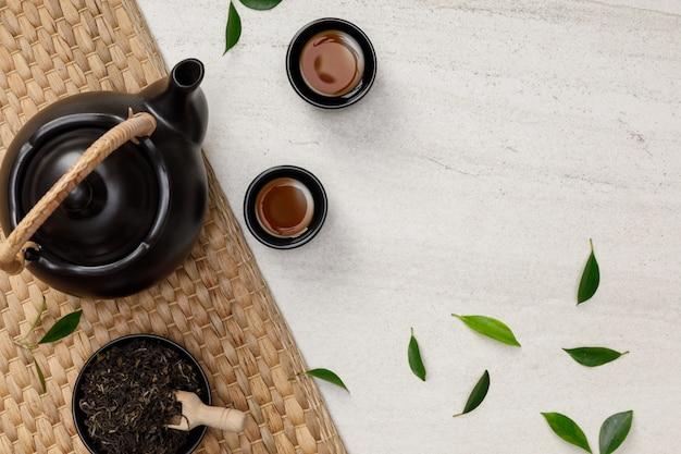 Theekop met theepot, biologische groene theebladeren en gedroogde kruiden op de witte steen lege ruimte creatieve plat leggen, biologisch product uit de natuur voor gezond met traditionele stijl
