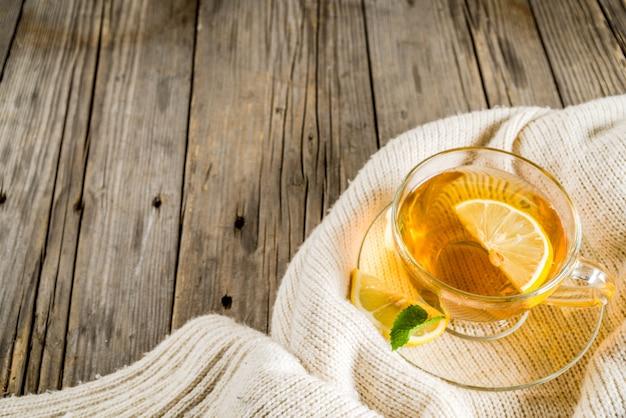 Theekopje met citroen, munt en kruiden, op oude rustieke houten tafel met warme dekens.