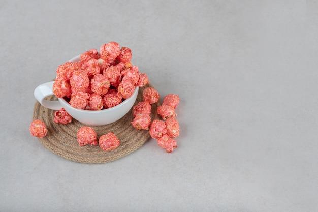 Theekopje op een onderzetter, gevuld met rode popcorn op marmeren tafel.