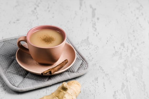 Theemasala in een kopje op het bord met de winterkruiden van kaneel en gember