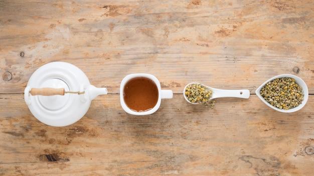 Theepot; citroen thee en gedroogde chinese chrysant bloemen gerangschikt in een rij op tafel