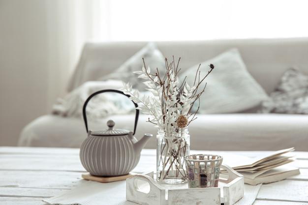 Theepot en decordetails op tafel in de woonkamer in hygge-stijl